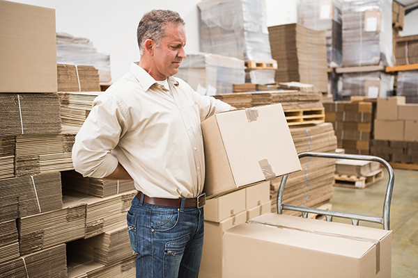 man with back pain lifting boxes in the workplace