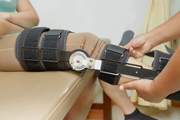 Orthopedic doctor with patient in knee brace